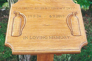 Photograph of a decorated wooden memorial plaque