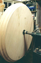 Photograph of a very large turned piece, mounted in a lathe